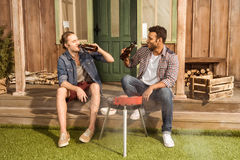 Young men drinking beer and preparing meat on outdoor grill Royalty Free Stock Photos