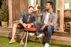 Young men drinking beer and preparing meat on outdoor grill Royalty Free Stock Images