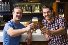 Young men drinking beer together. At the bar Stock Photo