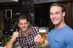 Young men drinking beer together. At the bar Stock Photos