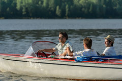 Men driving speed boat enjoying sunshine Stock Images