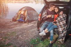 Young man embrace woman. They sit in trunk. Model is covered with blanket. Couple is at lake. There is tent at waterline. stock photography