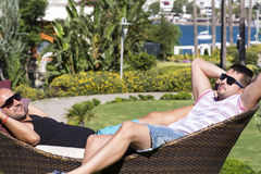 Young men   enjoying the summer vacation laying on sunbed in a tropical garden Stock Photography
