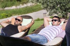 Young men   enjoying the summer vacation laying on sunbed in a tropical garden Stock Photos