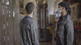 Young men in face masks standing in warehouse and talking. Professional experts discussing storage of finished