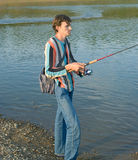 Young men fishes. The young men fishes a fishing tackle in the river Royalty Free Stock Photo