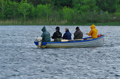 Young men fishing on a boat. CASTLEBAR,IE - CIRCA MAY, 2011 - Four people fishing from a boat in a lake in Ireland Royalty Free Stock Image
