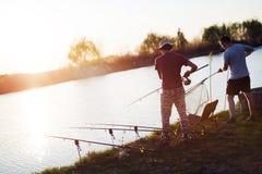 Young man fishing on lake at sunset enjoying hobby Stock Images