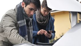 Young men fixing car engine royalty free stock image