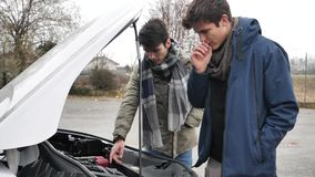 Young men fixing car engine. Young men looking up information while trying to repair car engine stock video