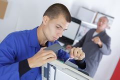 Young man fixing printing machine. Young men fixing a printing machine royalty free stock photography