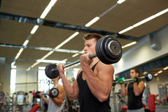 Young men flexing muscles with barbells in gym. Sport, bodybuilding, lifestyle and people concept - young men with barbells flexing muscles in gym Stock Photo