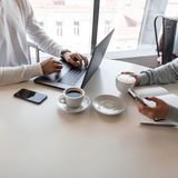 Young man freelancer remotely working at a laptop. Young business woman looks into the phone and drinks coffee with a colleague. Young men freelancer remotely stock image