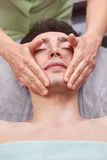 Young man getting face massaged. Stock Photo