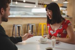 Man gifting ring to girlfriend in cafe Royalty Free Stock Images