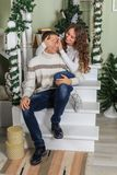 Young man and a young girl are sitting on the steps of a white staircase in a house in the eve of New Year holidays. Girl closed t. Young men and a young girl royalty free stock photography