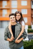 Young man giving girlfirend piggyback ride in city street stock photos