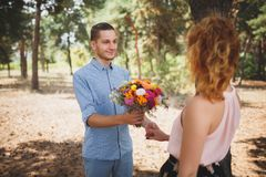 A young couple is standing in a forest with flowers. The guy gave flowers to his girlfriend. A beautiful autumn day. Stock Photography