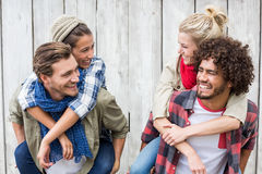 Young men giving piggyback to women Stock Photography