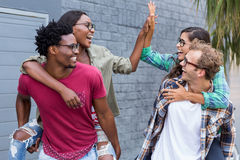 Young men giving piggyback to women. Portrait of young men giving piggyback to women stock photo