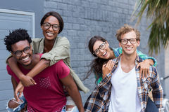 Young men giving piggyback to women Royalty Free Stock Image