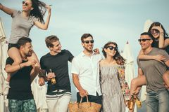 Group of Friends Walking at Beach, having fun, womans piggyback on mans, funny vacation. Young men giving their girlfriends piggyback rides beach. Cheerful stock photography