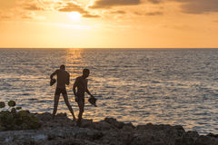 Young men go swimming at Sunset stock image
