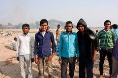 Young men group walk through the sandy field was o Stock Photos