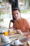 Young men having breakfast at resort restaurant Royalty Free Stock Photos