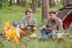 Young men are heated in a fire and cook out on a summer camp Stock Photos