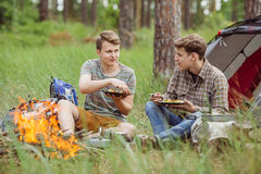 Young men are heated in a fire and cook out on a summer camp Royalty Free Stock Images