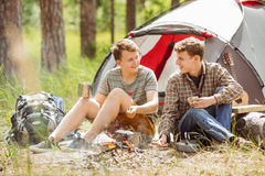 Young men are heated in a fire and cook out on a summer forest Royalty Free Stock Photos