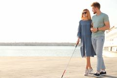 Young man helping blind person with long cane in city royalty free stock photo