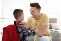 Young man helping his little child get ready. Young men helping his little child get ready for school at home Stock Photo