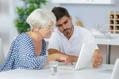 Young man helping senior lady to use laptop. Young men helping senior lady to use a laptop stock photo