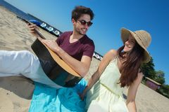 Young man with guitar and girlfriend on beach Royalty Free Stock Photos