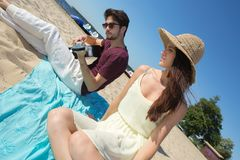 Young man with guitar and girlfriend on beach Royalty Free Stock Photo