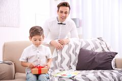 Young man and his little son with gift for Father`s Day. Young men and his little son with gift for Father`s Day at home Royalty Free Stock Photography