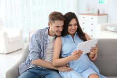 Young man and his pregnant wife using tablet computer. Young men and his pregnant wife using tablet computer on sofa at home stock photo