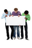 Young men holding up a blank sign Royalty Free Stock Photo