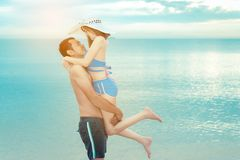Young man hugging girlfriend romantic couple. Young men hugging girlfriend romantic couple honeymoon on beach in vacation relaxation in summer season Stock Photography