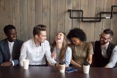 Caucasian man joking at cafe meeting making multiracial friends Royalty Free Stock Images