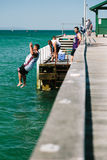 Young men jumping off jetty into water. MELBOURNE/AUSTRALIA - FEBRUARY 6: Youths jump off a jetty into the water, while others fish in Mordialloc, a coastal royalty free stock image