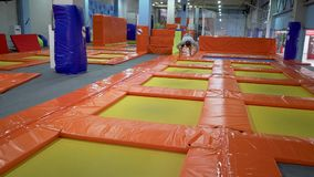 Young Men Jumping At Trampoline In Indoors Playground. Active People Male Having Fun At Sport Center. Slow Motion
