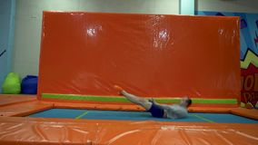 Young Men Jumping At Trampoline In Indoors Playground. Active People Male Having Fun At Sport Center. Slow Motion stock video footage