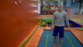 Young Men Jumping At Trampoline In Indoors Playground. Active People Male Having Fun At Sport Center. Slow Motion stock video