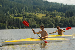 Kayaking sporty men on river sunshine Stock Images