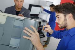 Young man learning to fix photocopier. Young men learning to fix a photocopier Royalty Free Stock Photography