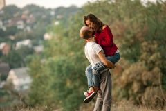 Young man lifted up girl and they kiss on walk in forest. Royalty Free Stock Images