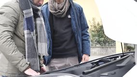 Young men fixing car engine. Young men looking up information while trying to repair car engine stock footage